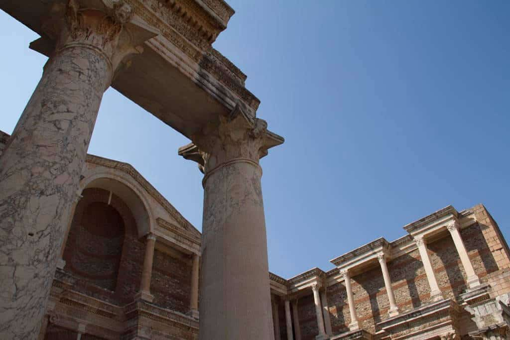 """A view of marble columns and the façade, part of an ancient gymnasium in Sardis. A gymnasium was roughly equivalent to a high school, but with a strong emphasis on preparation for public athletic games (hence the modern use of the word """"gymnasium"""")."""