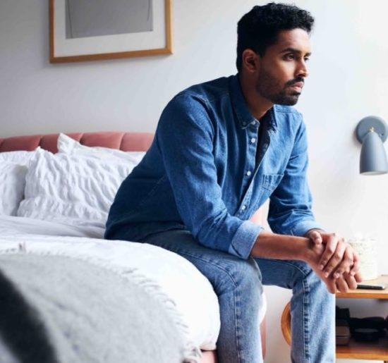 pastor sitting on the edge of his bed thinking about his mental health